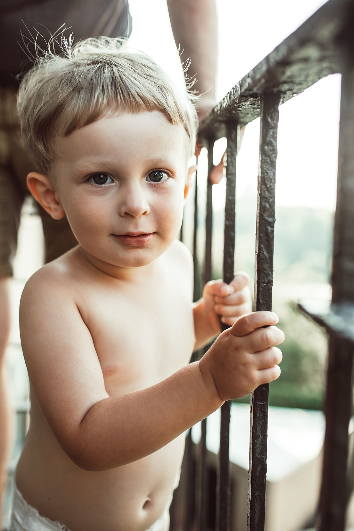 portrait shot of toddler son holding railing on his fire escape. image by krystil mcdowall photography