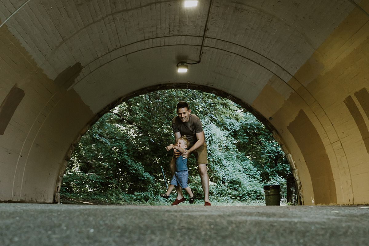 dad and son playing in tunnel and being goofy. having a fun dad and son family session with nyc family and newborn photographer krystil mcdowall