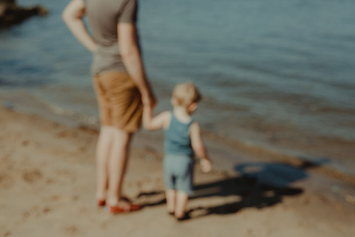 blurred focus of dad and son at the hudson river in nyc, holding hands while in the sand