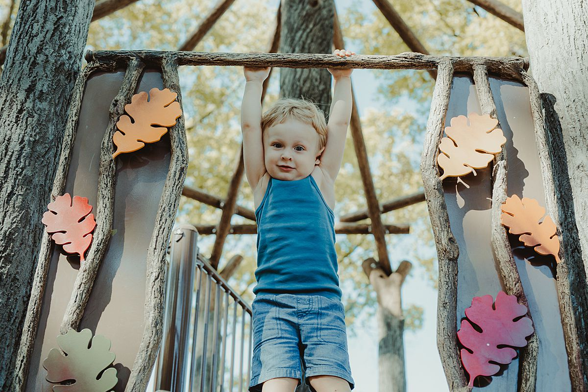 son swings at the top of the slide at discovery park in nyc during family lifestyle session