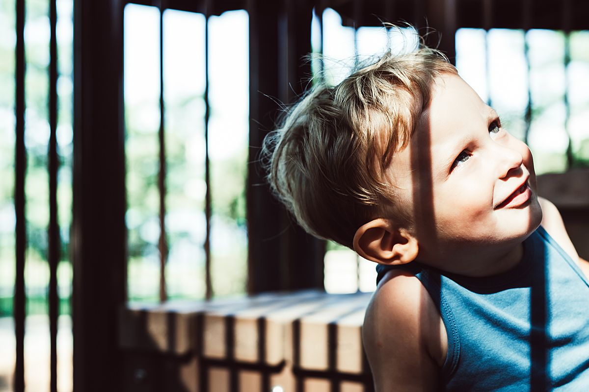 toddler in discovery playground in nyc caught amongst pockets of sun and shade and looking up playfully in nyc family lifestyle session