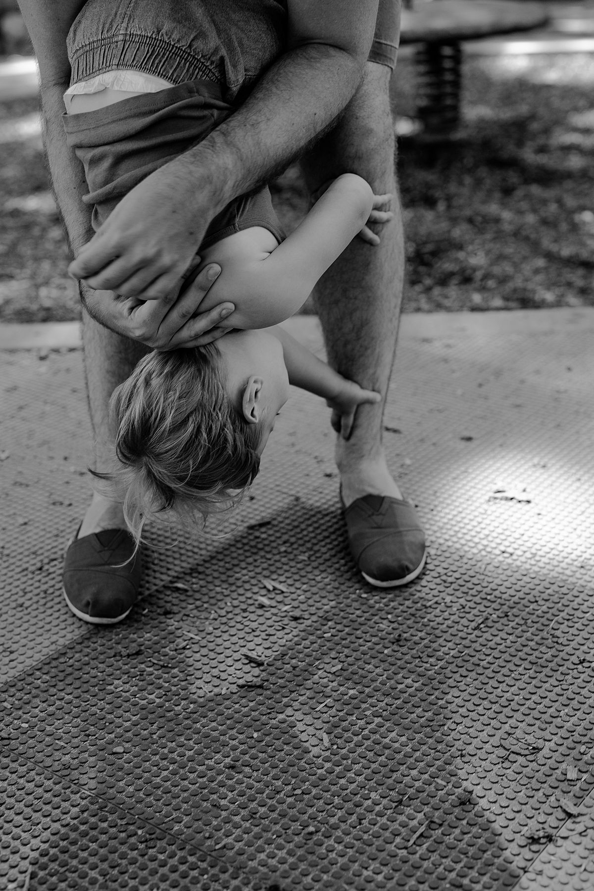 black and white image of son enjoying shoulder ride from dad in playground. capturing fleeting family moments is nyc family and newborn photographer krystil mcdowall photography