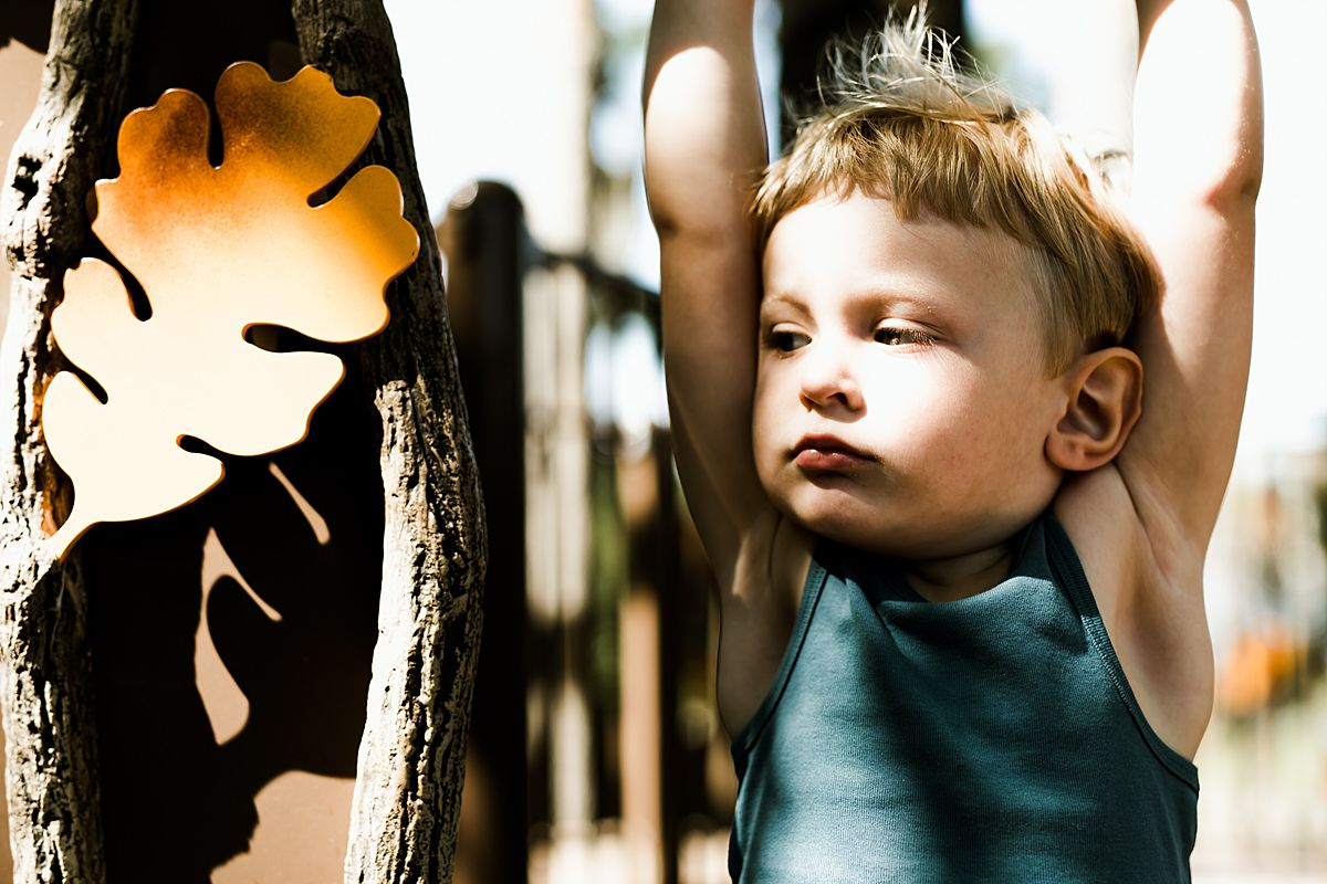 boy plays on playground and looks curiously at leaf in playground. image by krystil mcdowall