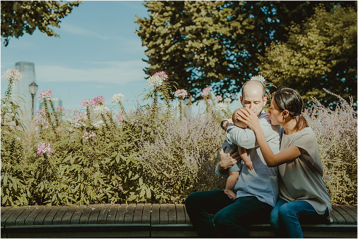 mom, dad and son sit sweetly on park bench all cuddled together during family lifestyle session with krystil mcdowall photography