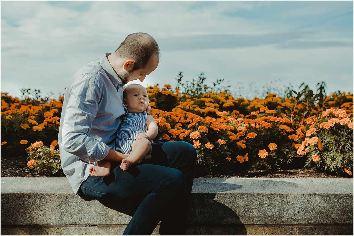 dad and son sitting in front of colorful garden bed during family lifestyle session with krystil mcdowall photography in nyc
