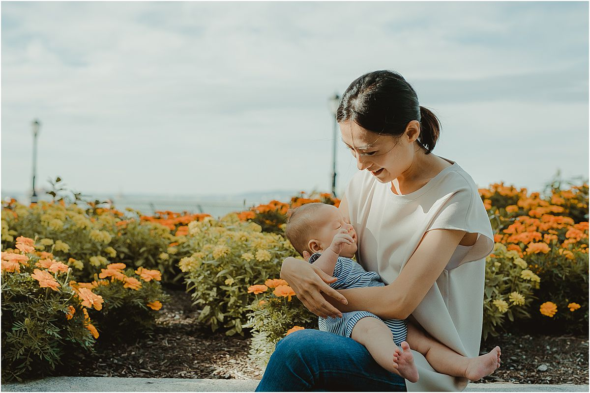 mom and son sit cuddled together in front of colorful flower bed during nyc family lifestyle session with krystil mcdowall photography