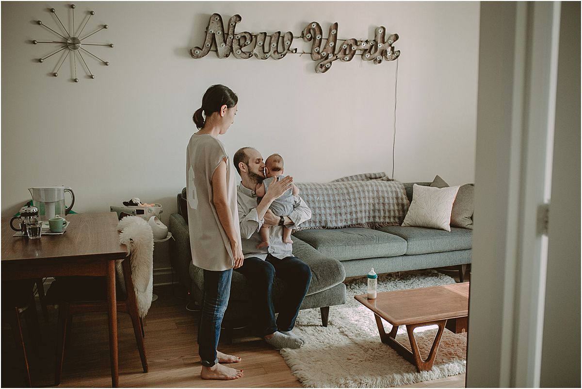 three month old baby boy rests with mom and dad during feeding time at home during family lifestyle session by nyc family and newborn photographer krystil mcdowall