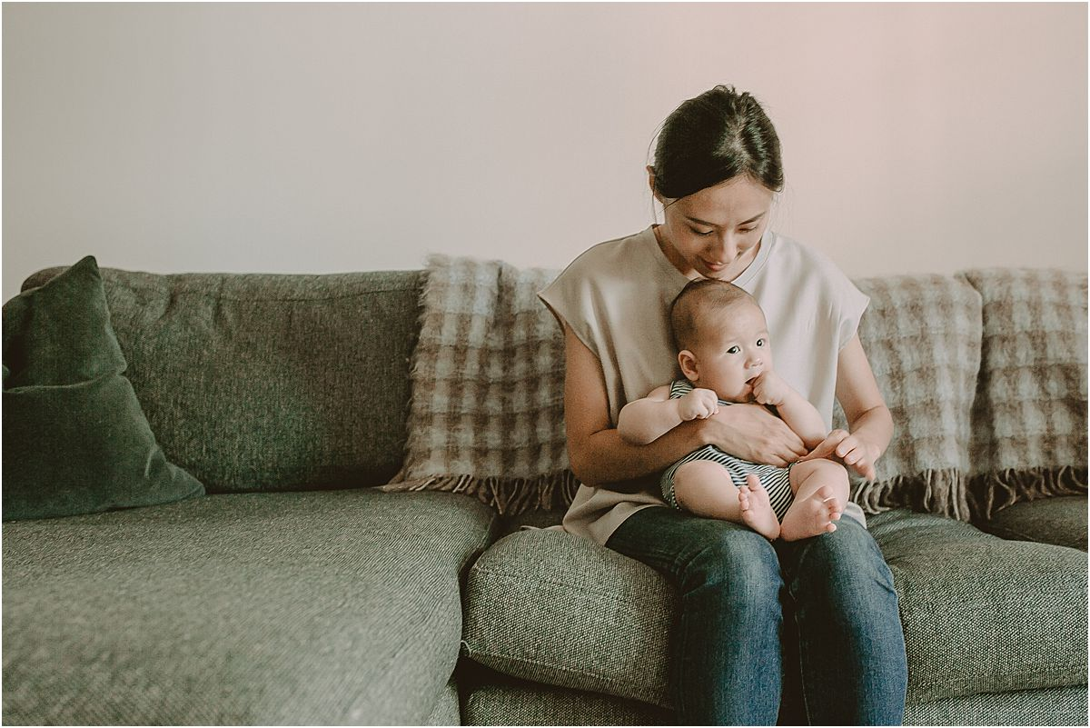 mom and son portrait sitting cozy on the couch in their downtown manhattan abode. image by nyc family photographer krystil mcdowall