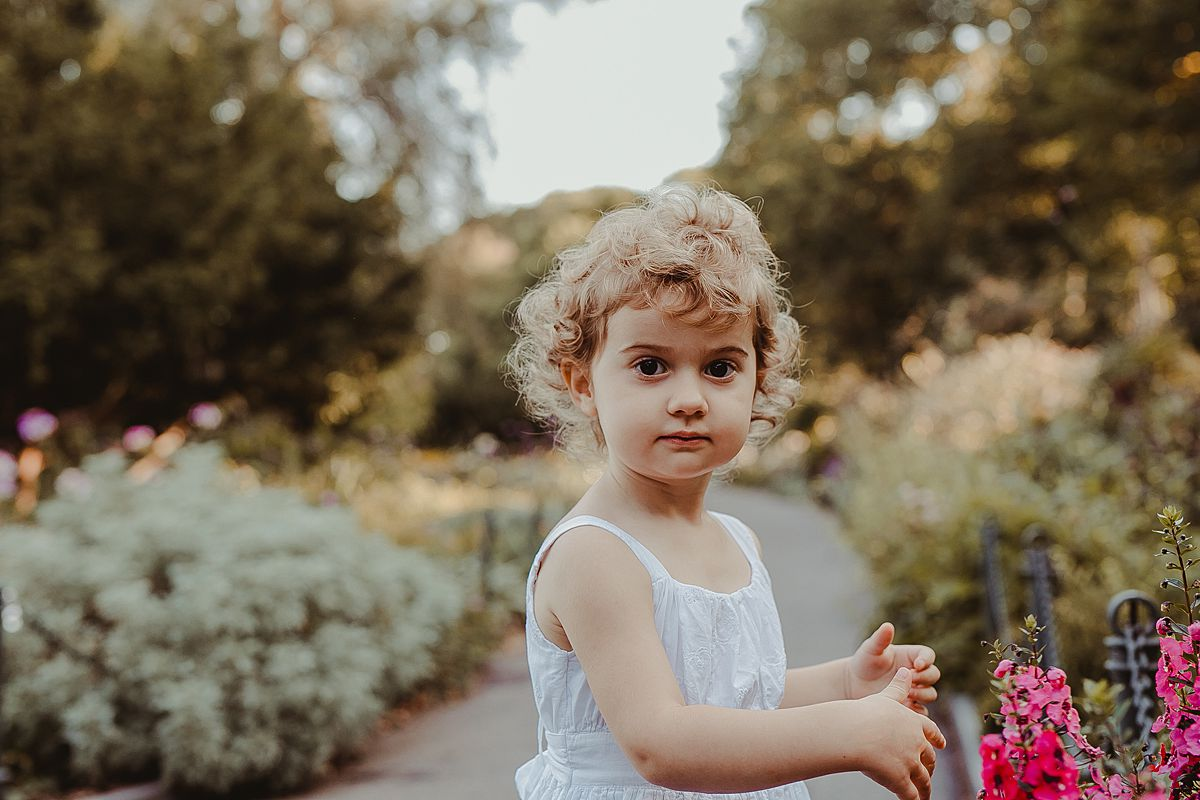 beautiful toddler girl plays amongst bright flowers in family session in fort tryon park. image by krystil mcdowall photography