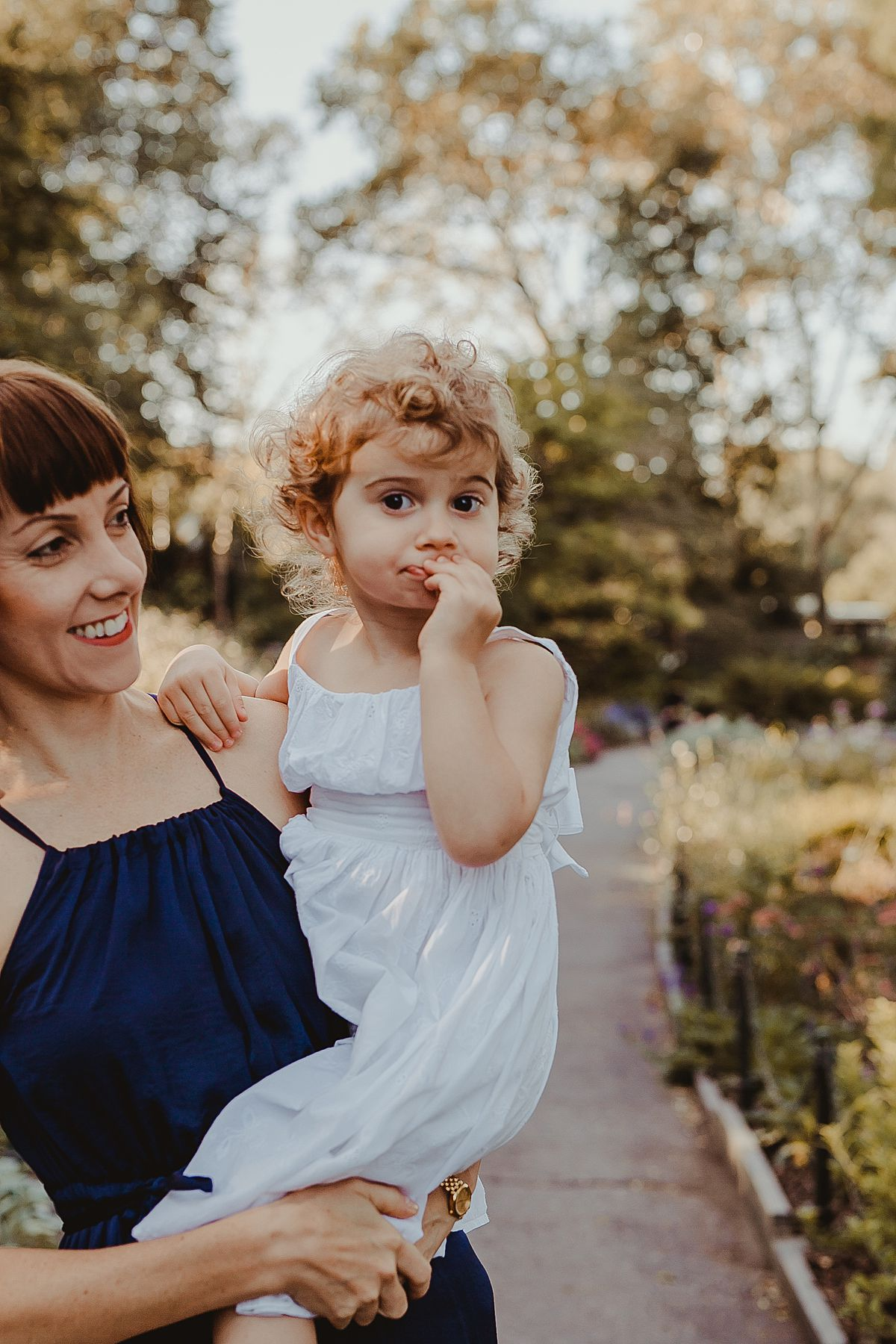 mom holds daughter amongst bright and colorful park flowers in park during documentary family session. image by nyc family and newborn photographer krystil mcdowall