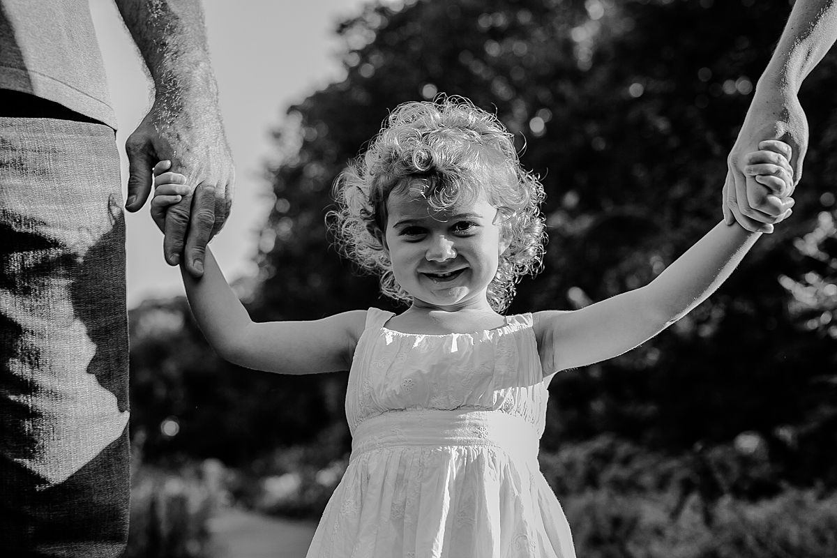 daughter holds mom and dad's hands in park. image by nyc family and newborn photographer krystil mcdowall