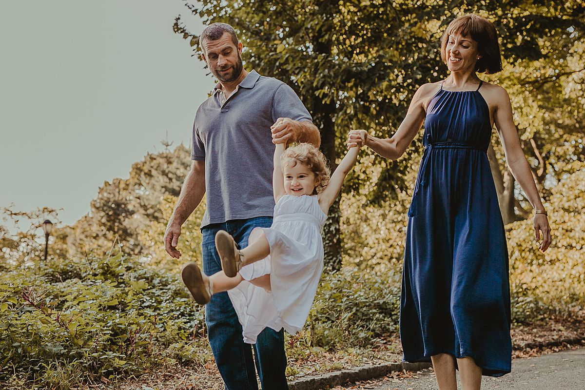 mom and dad swing daughter among fall leaves in the park during candid family session with photographer krystil mcdowall