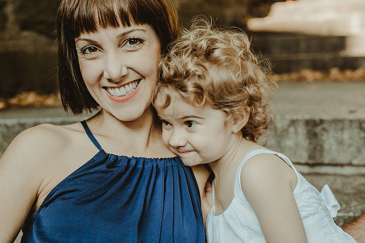 portrait of mom and daughter sitting on the park stairs among fall leaves during documentary family session with krystil mcdowall photography