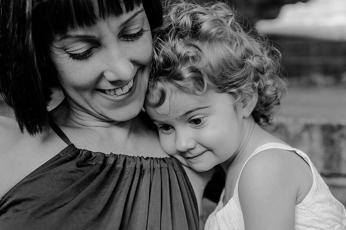 black and white portrait of mom and daughter sitting on the park stairs among fall leaves during documentary family session with krystil mcdowall photography