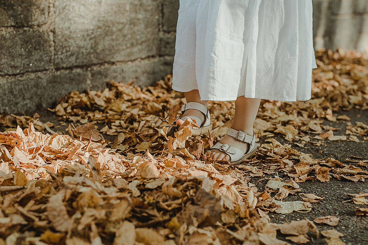 close up of daughter's feet in white sandals jumping in the leaves of an nyc park
