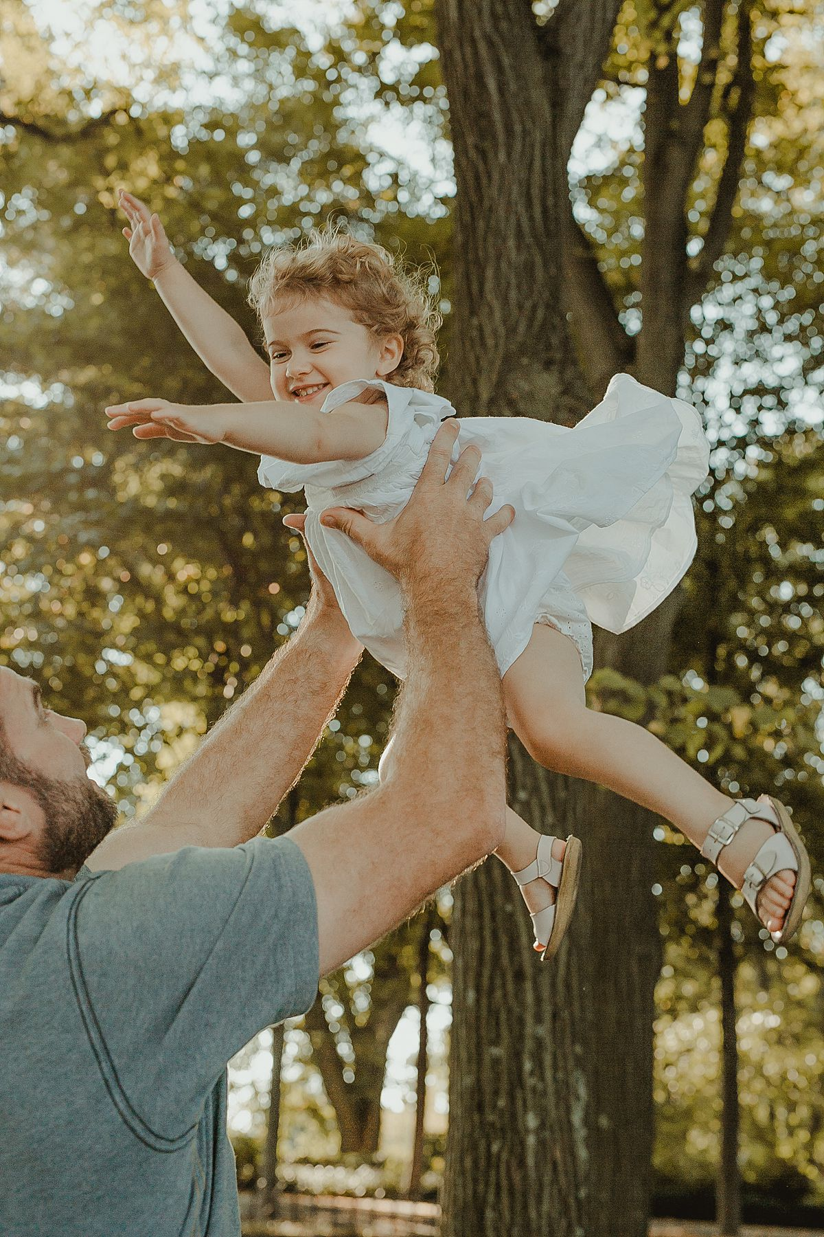 dad throws daughter in the air in fun family outdoor in nyc. photo by krystil mcdowall photography