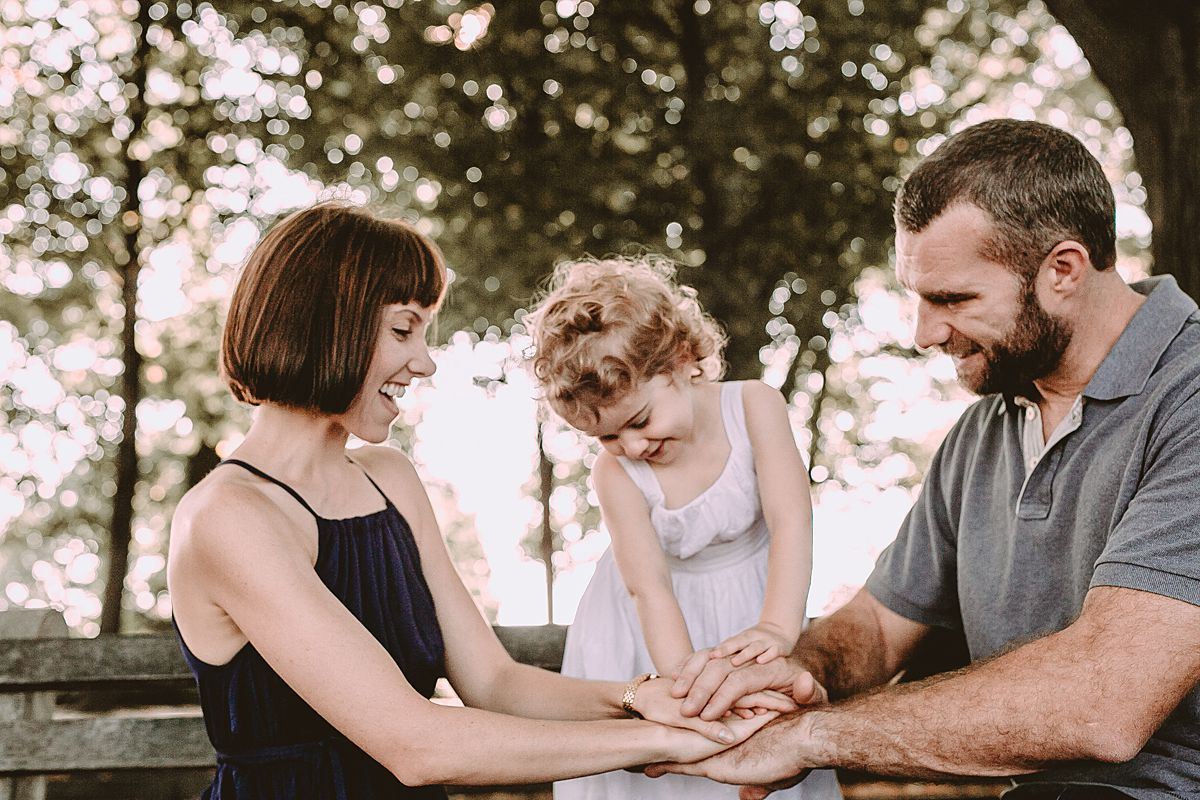 mom, dad and daughter sit on park bench playing the hand game. capturing real family moments in new york city