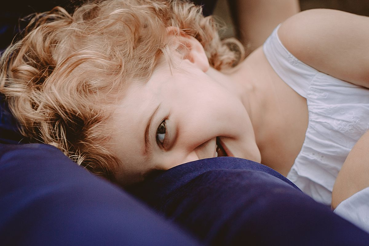 close up of cheeky daughter laying on mom's lap. photo by nyc family and newborn photographer krystil mcdowall