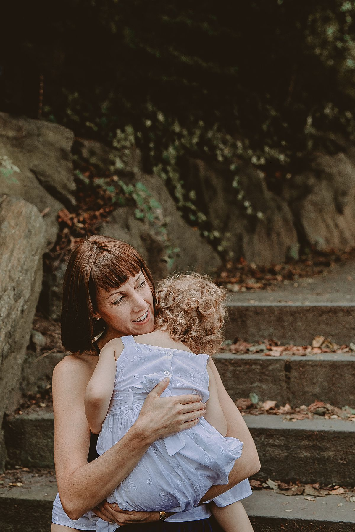 close up of mom and daughter cuddling on park stairs in fort tryong par during family lifestyle session. image by photographer krystil mcdowall