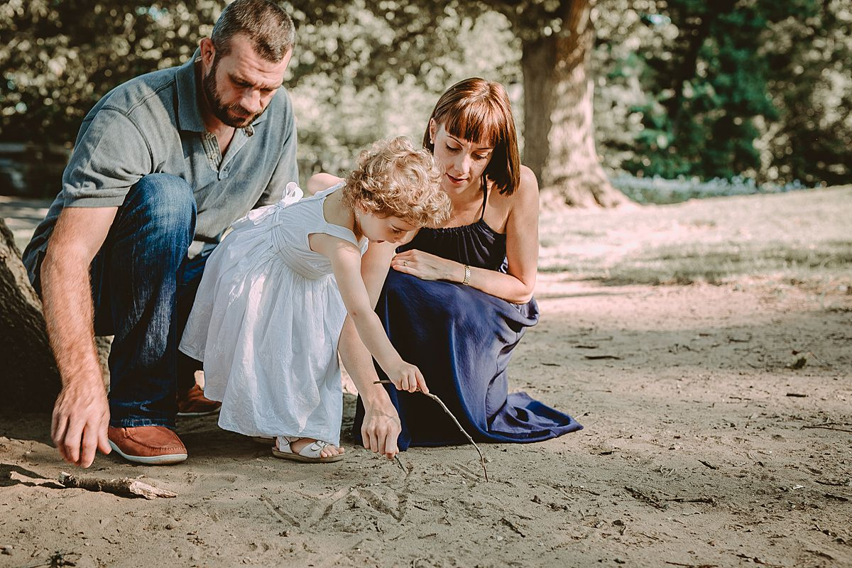 candid family photo of daughter, mom and dad playing in dirt in the park. capturing candid family moments for nyc families is krystil mcdowall photography