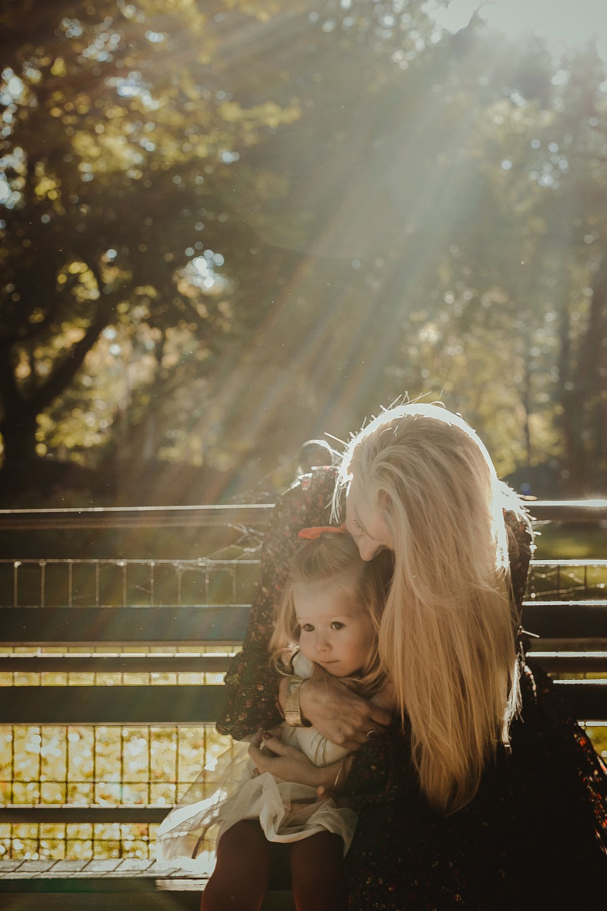 mom and daughter enjoying cuddles and sun streams in behind them sitting on park bench in central park nyc. photo by nyc family photographer krystil mcdowall