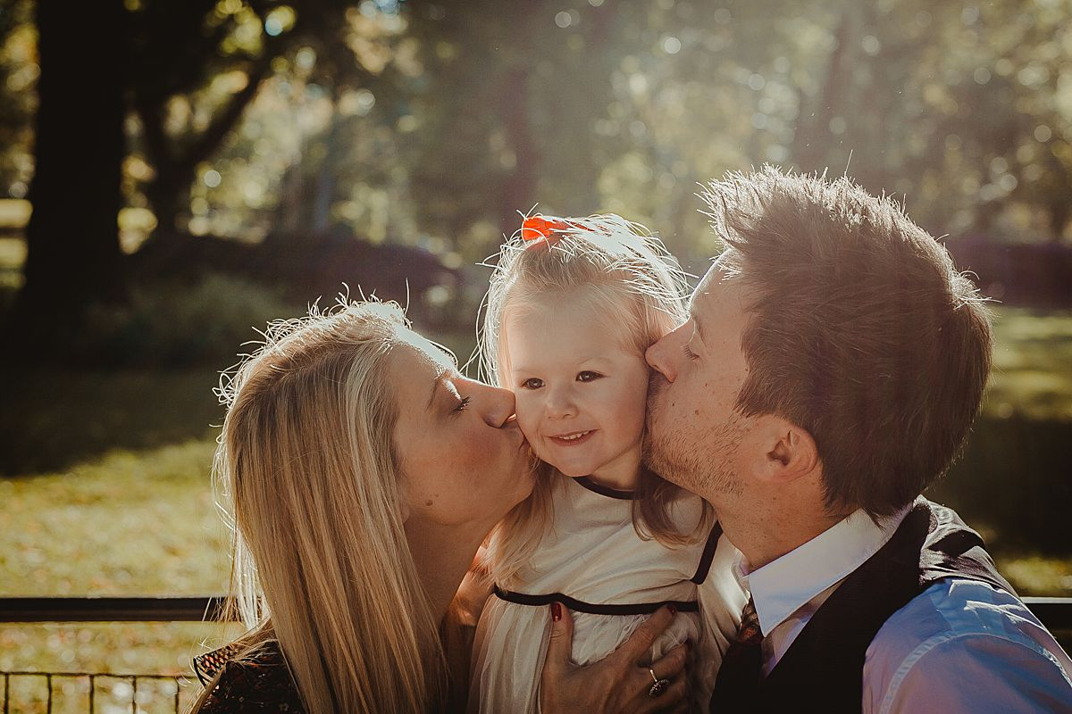 mom and dad kissing beautiful blonde daughter on sunny morning in central park. image by nyc family photographer krystil mcdowall