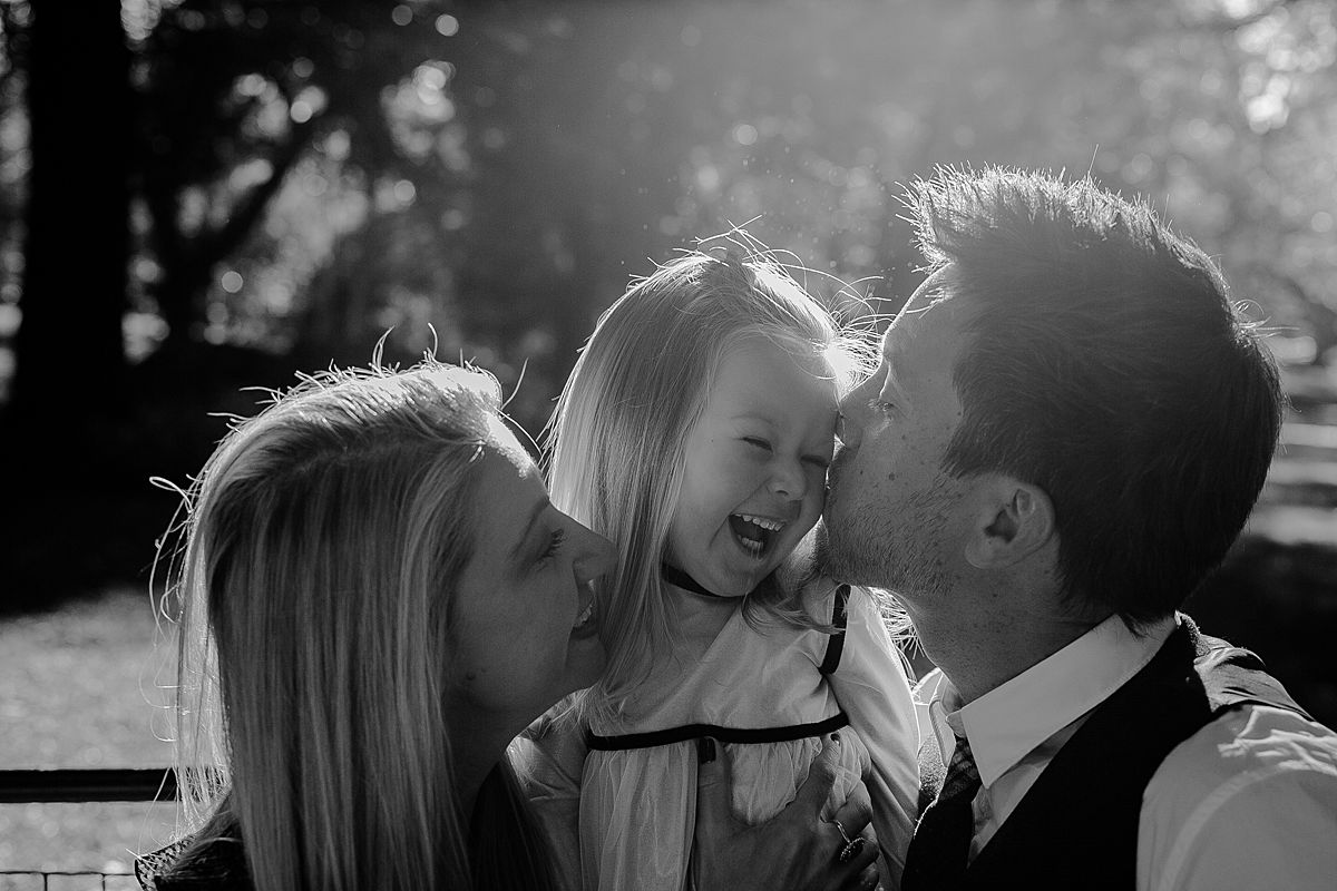 daughter, mom and dad enjoy laughter and cuddles on park bench in nyc. image by nyc family photographer krystil mcdowall photography