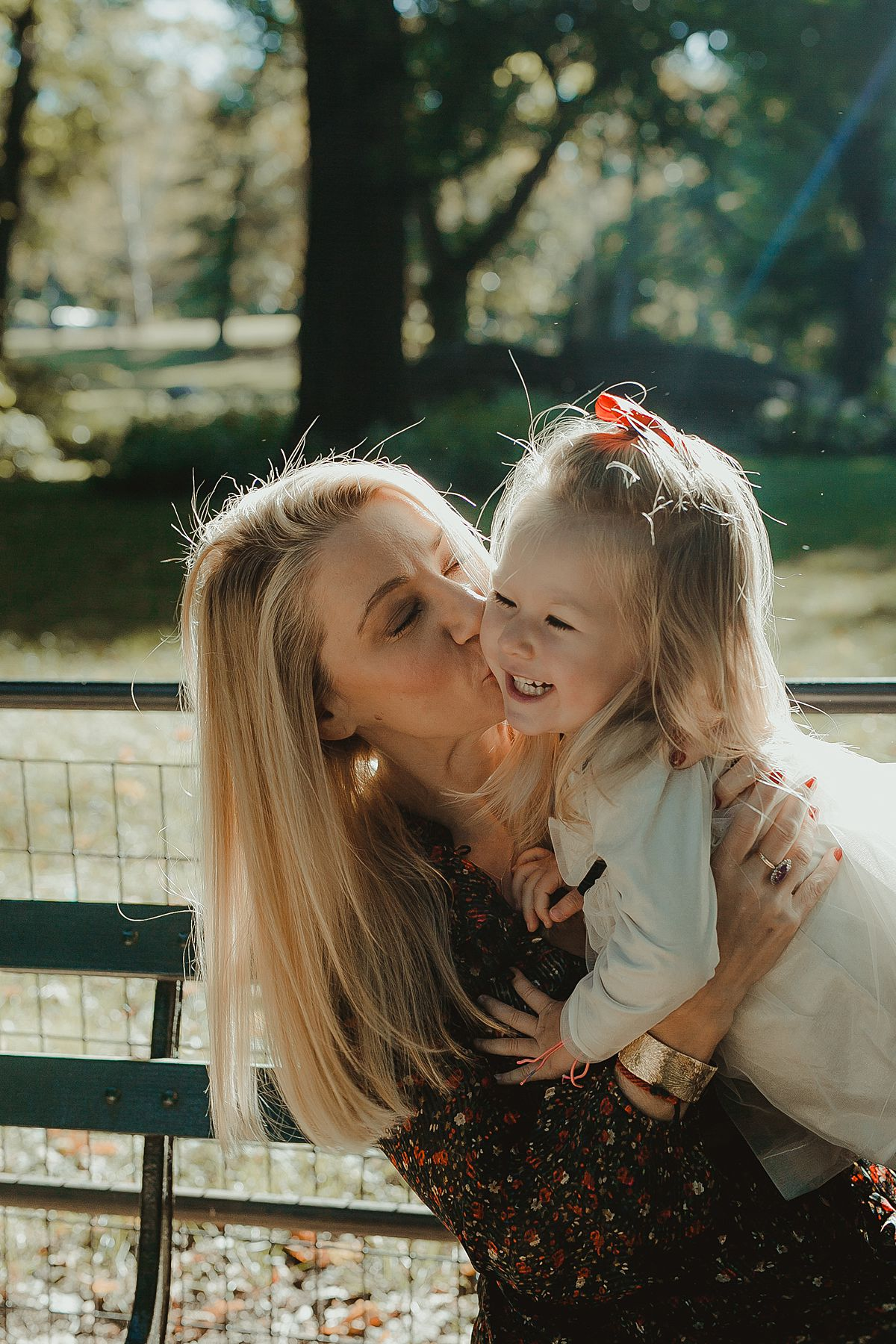 mom kissing daughters cheek with sun streaming in the background during sunny morning session is central park nyc