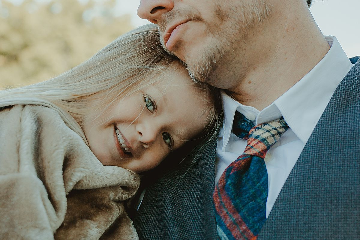 portrait of beautiful blonde daughter cuddling into dad while looking at the camera. image by nyc family photographer krystil mcdowall