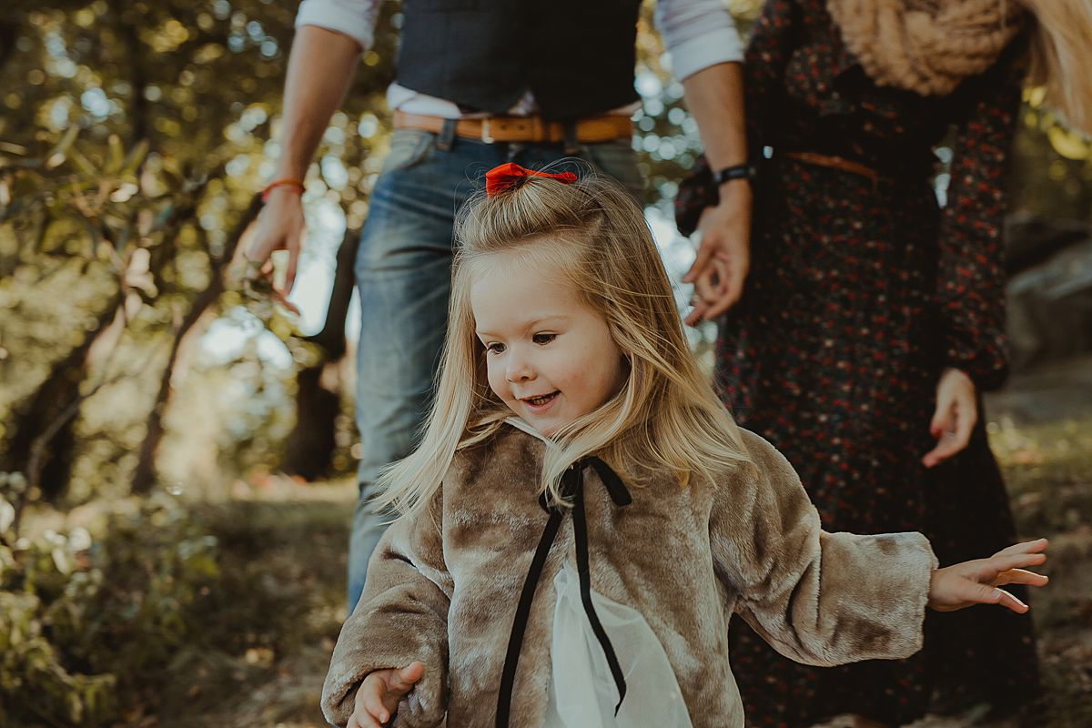daughter running down small hill in nyc's central park during family photo session with krystil mcdowall photography