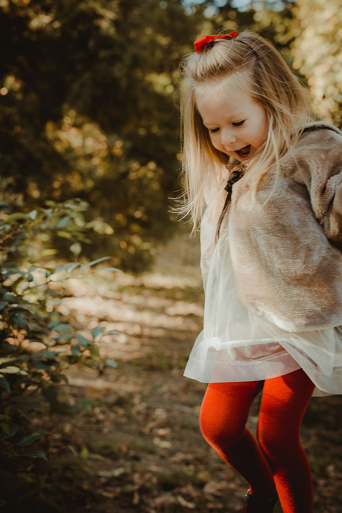 candid photo of beautiful blonde toddler with red tights and ribbon in her hair playing in central park. nyc family photographer krystil mcdowall