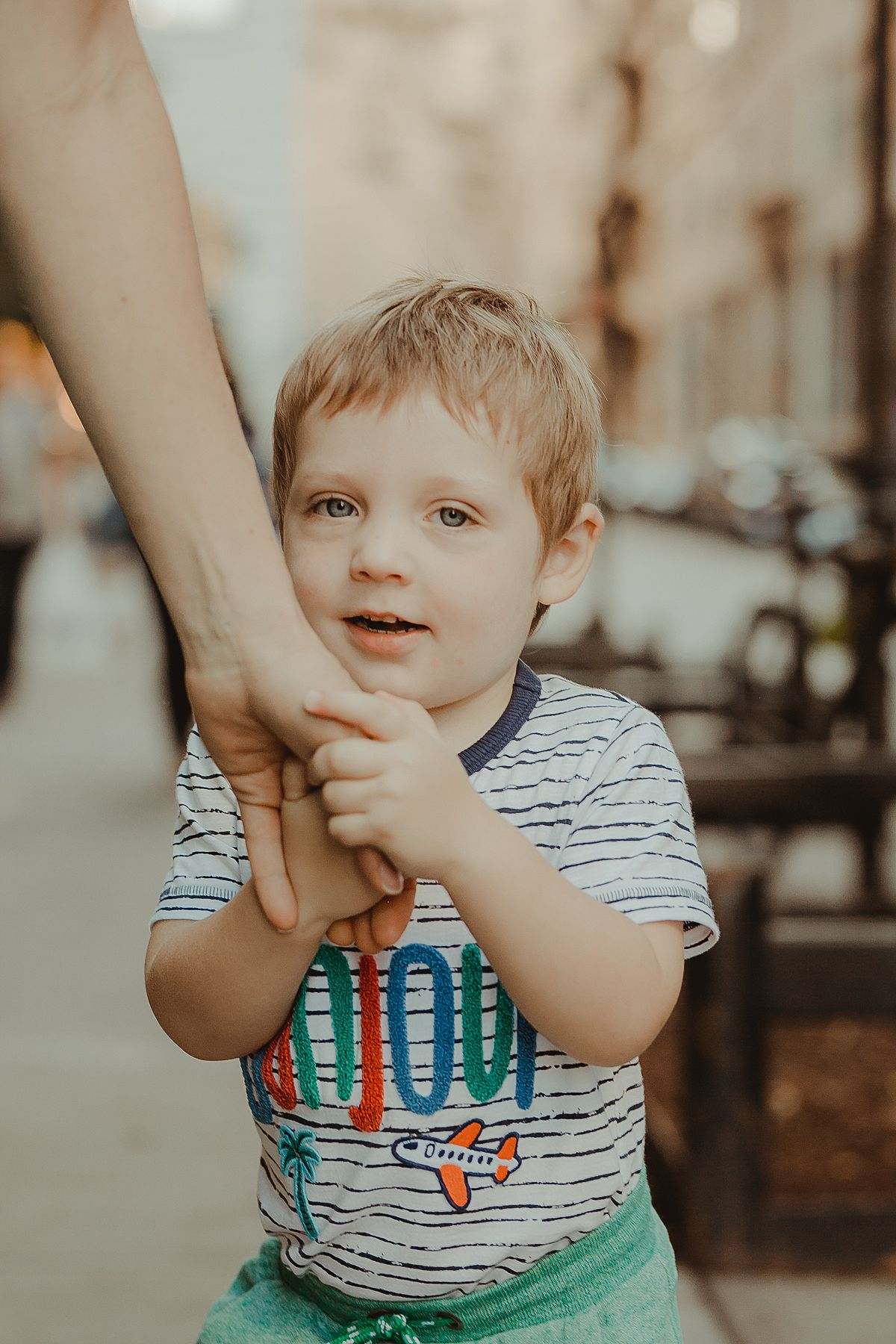 boy in colorful bonjour shirt holds his mom's hand and smiles for the camera in documentary photo shoot in brooklyn. image by krystil mcdowall photography
