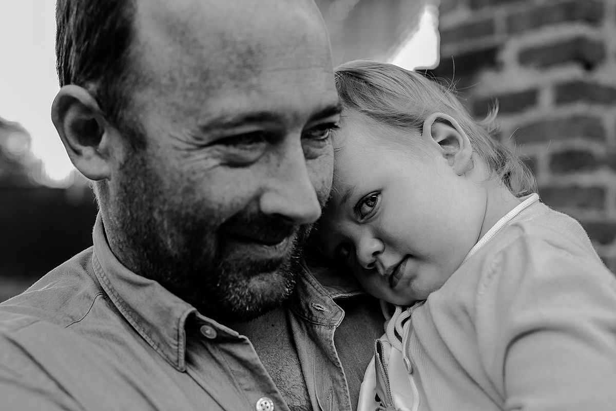 black and white portrait f girl cuddling up to dad in brooklyn during documentary photo shoot in brooklyn. image by krystil mcdowall photography