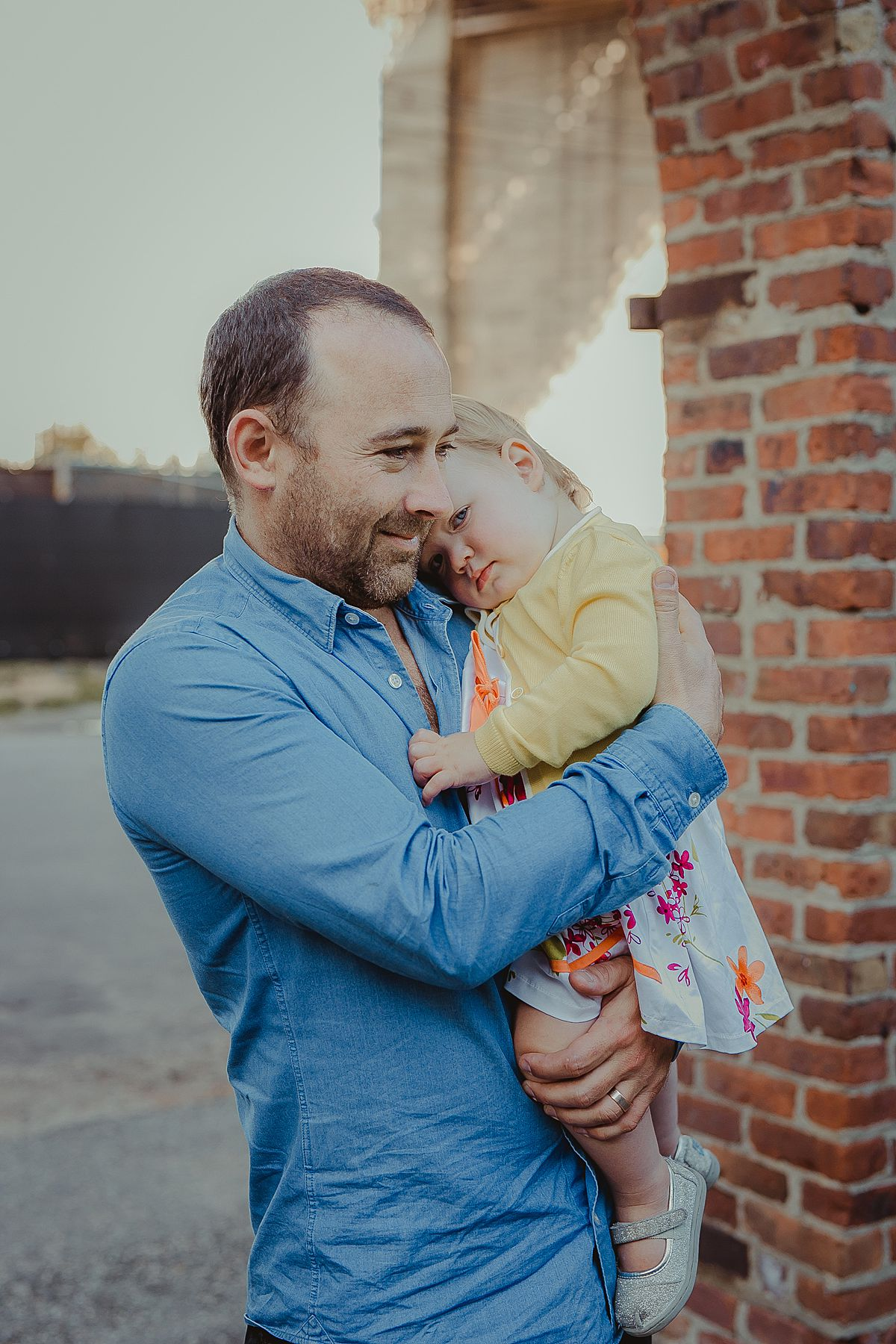 image of girl cuddling into her dad against a brick backdrop in dumbo brooklyn. image by nyc newborn and family photographer krystil mcdowall