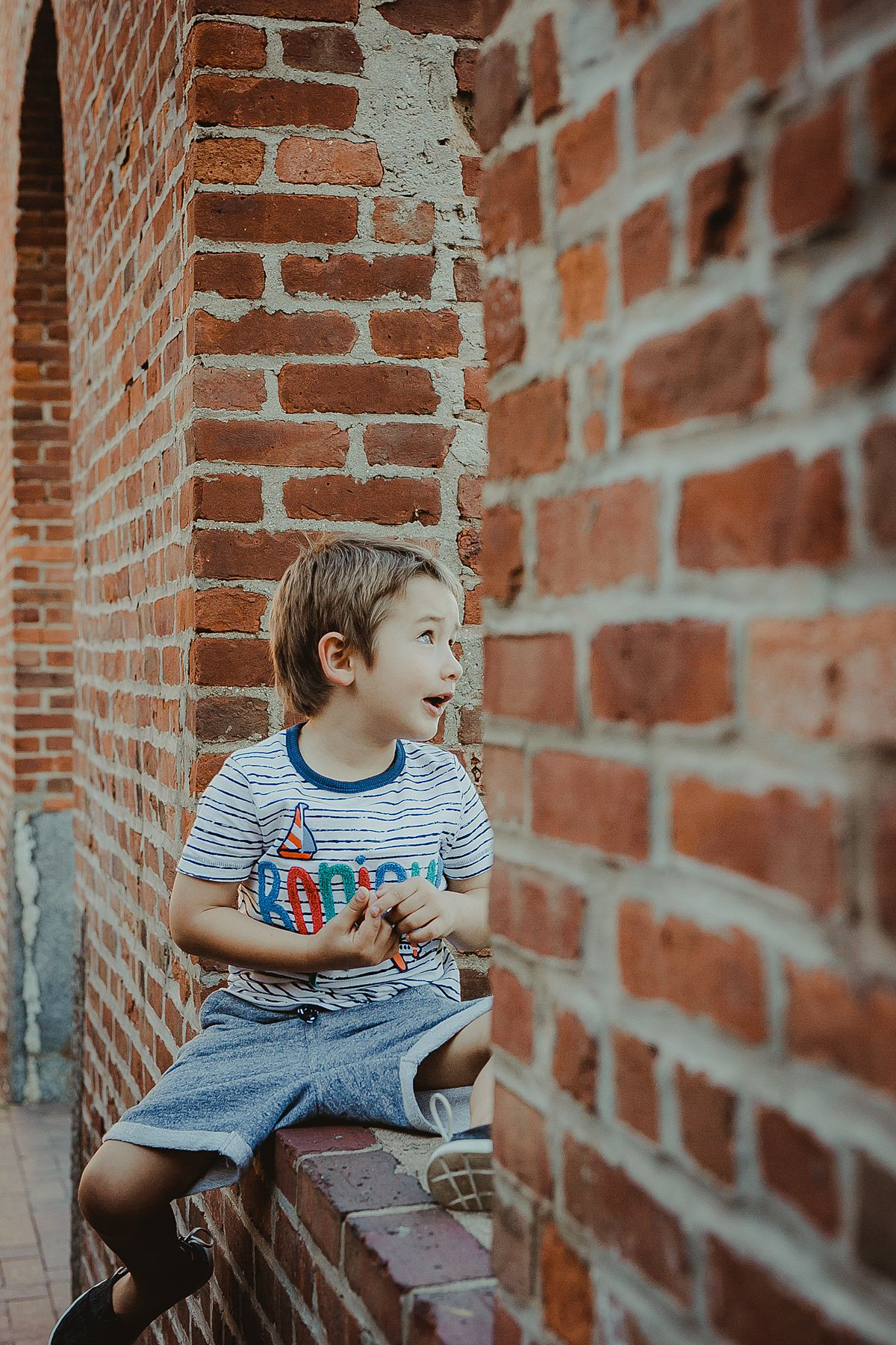 boy sits in brick wall window looking out at the east river during candid fun family session with krystil mcdowall photography