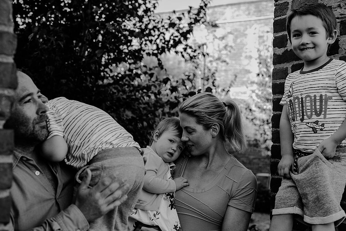 family sits in brick wall window looking out at the east river during candid fun family session with krystil mcdowall photography