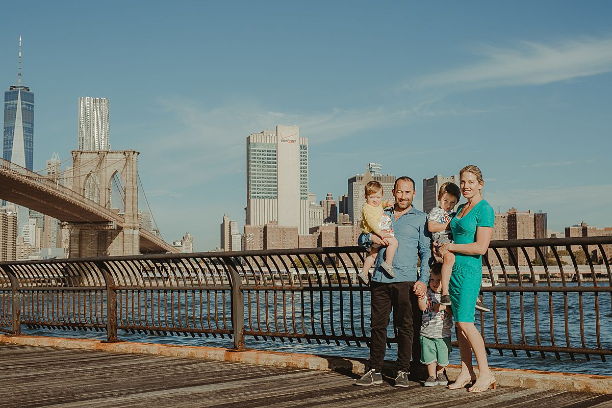 family stands on brooklyn promenade with east river and manhattan skyline in the background. photo by nyc family and newborn photographer