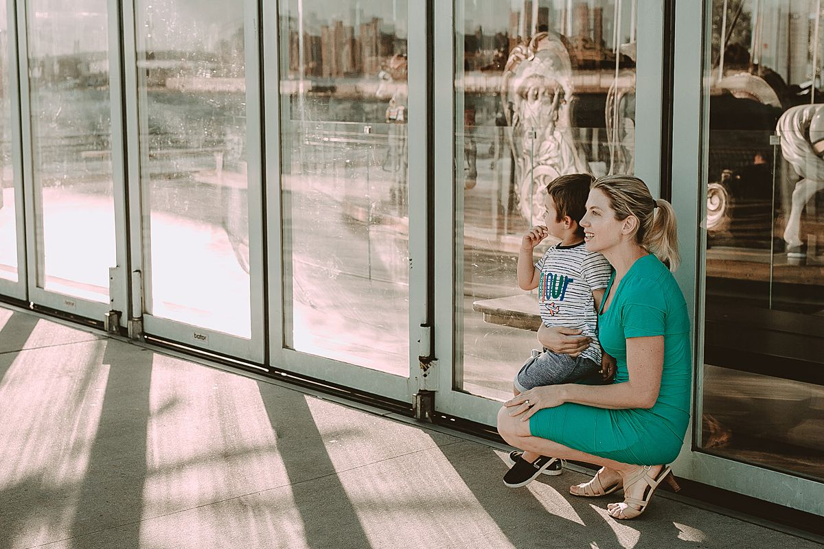 mom and son exploring jane's carousel at the brooklyn promenade. photo by nyc family and newborn photographer