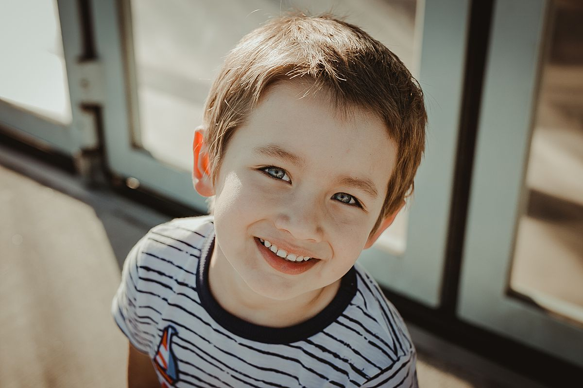 portrait of boy out front of jane's carousel in dumbo brooklyn. photo by nyc family photographer krystil mcdowall