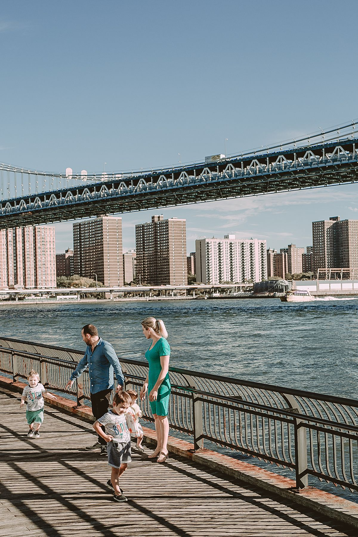 candid photo of family of five walking along the brooklyn promenade.portrait of son with mum and dad out front of jane's carousel dumbo brooklyn. photo by nyc family photographer krystil mcdowall