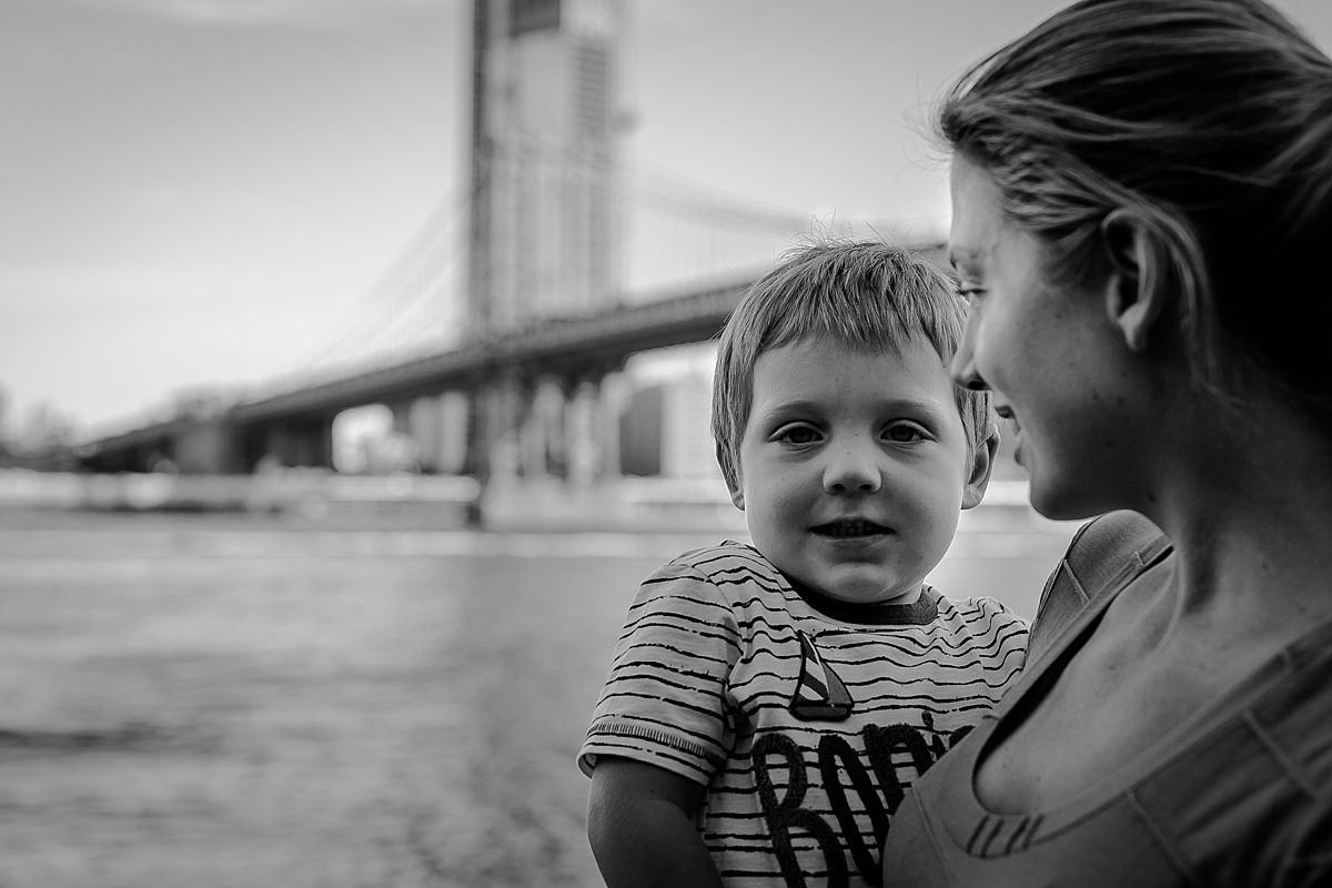 portrait of mon and toddler son standing in front of the manhattan bridge. photo by nyc family photographer krystil mcdowall