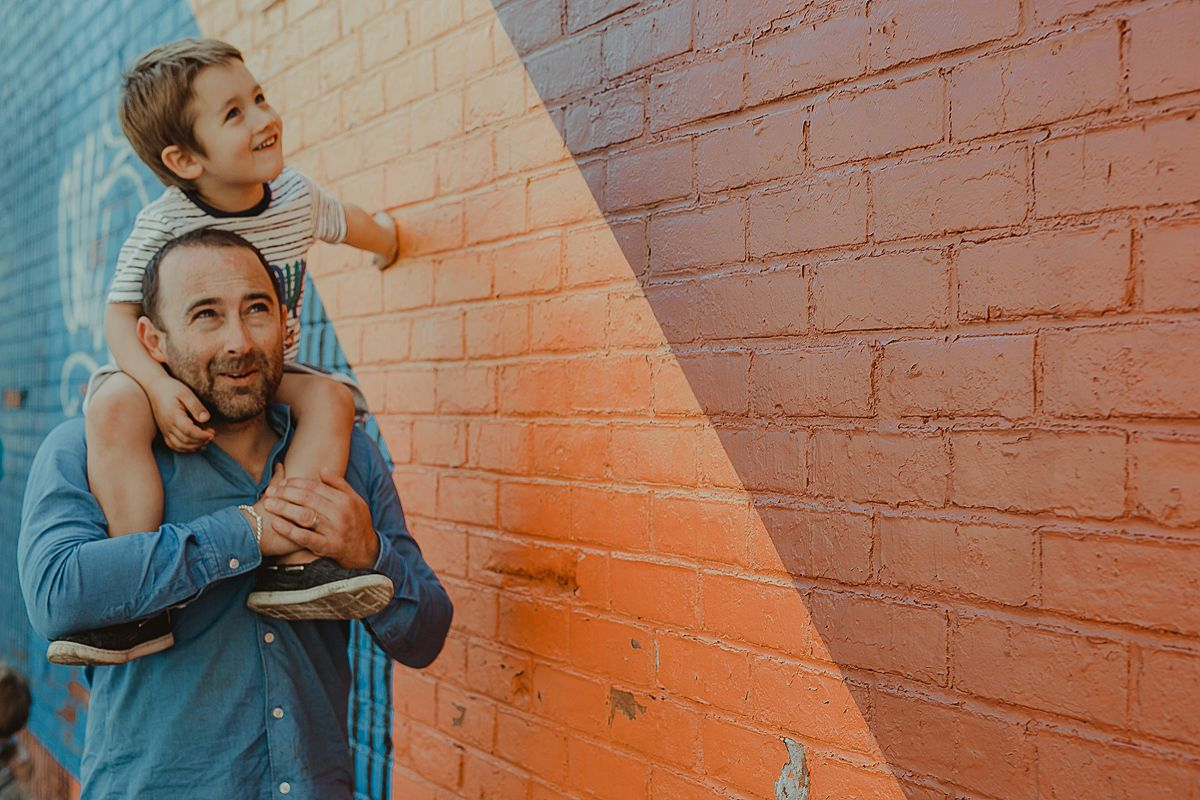dad giving son a shoulder ride in front of colorful graffiti wall in dumbo brooklyn. image by krystil mcdowall photography