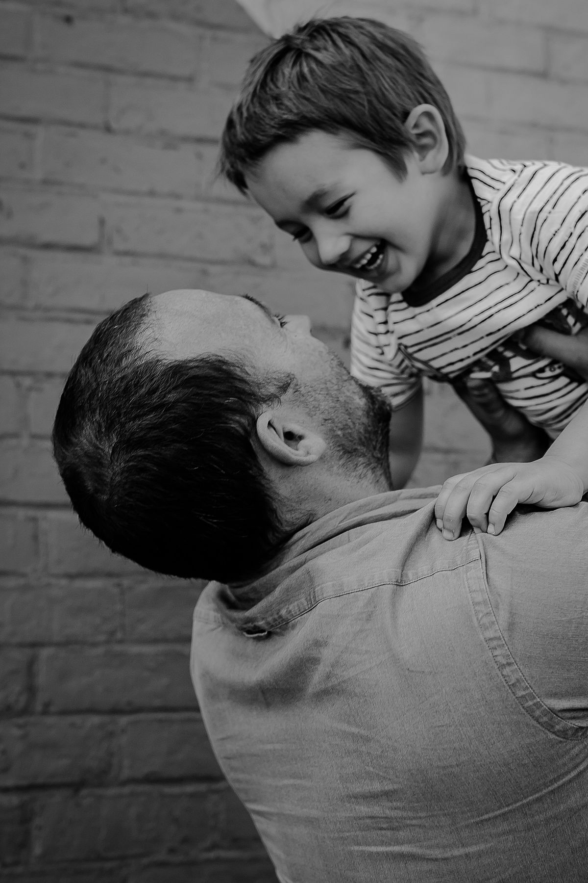 dad holds son in air and both laugh happily. image by nyc family photographer krystil mcdowall
