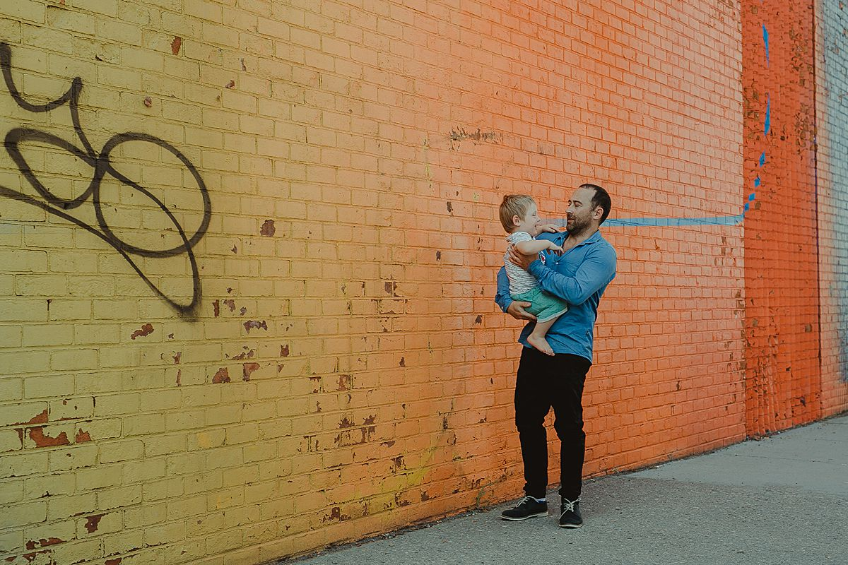 dad and son portrait in front of colorful graffiti wall in dumbo brooklyn. image by nyc family photographer krystil mcdowall