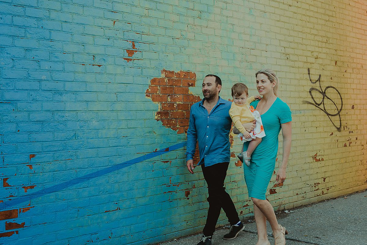 mom, dad and daughter in front of colorful graffiti wall in dumbo brooklyn. image by nyc family photographer krystil mcdowall