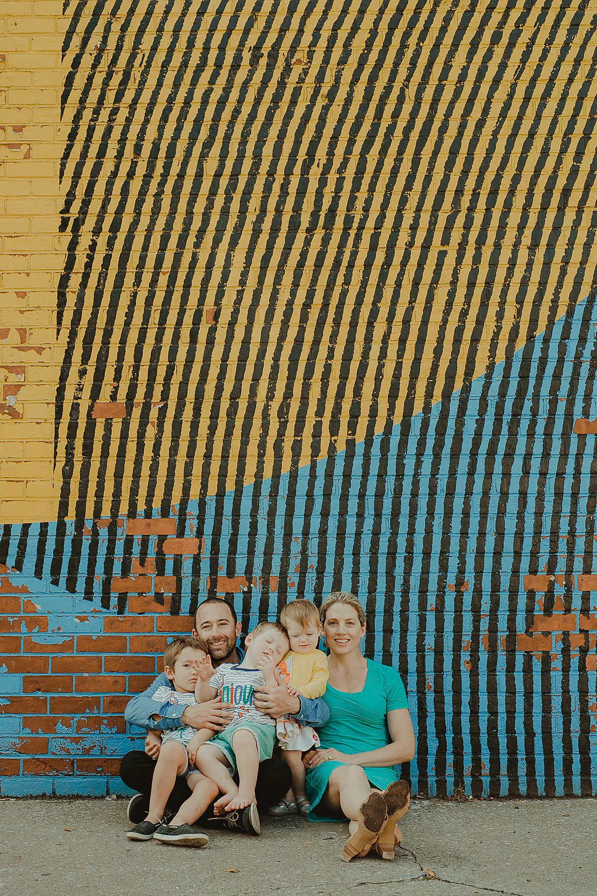 family portrait in front of colorful graffiti wall in dumbo brooklyn. image by nyc family photographer krystil mcdowall