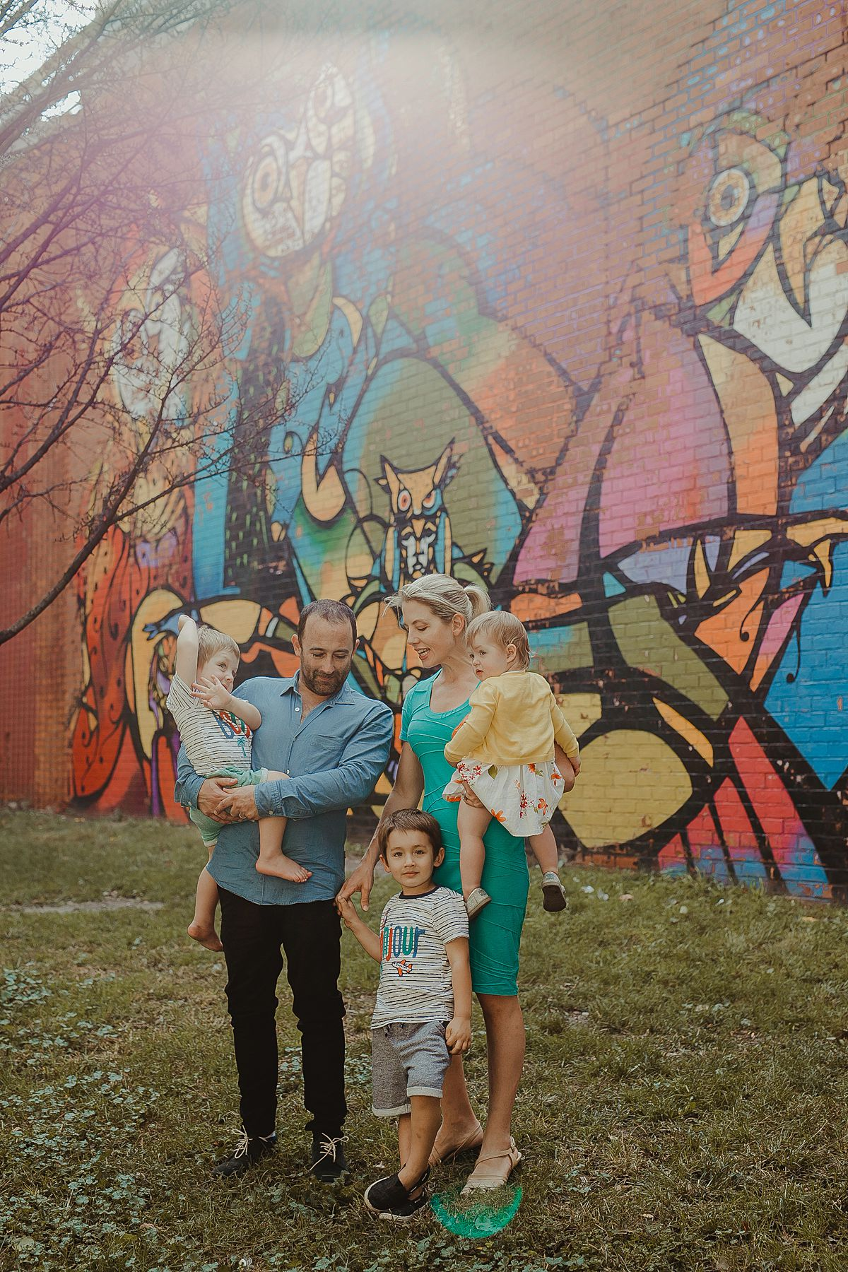 sun drenched family portrait in front of colorful graffiti wall in new york city