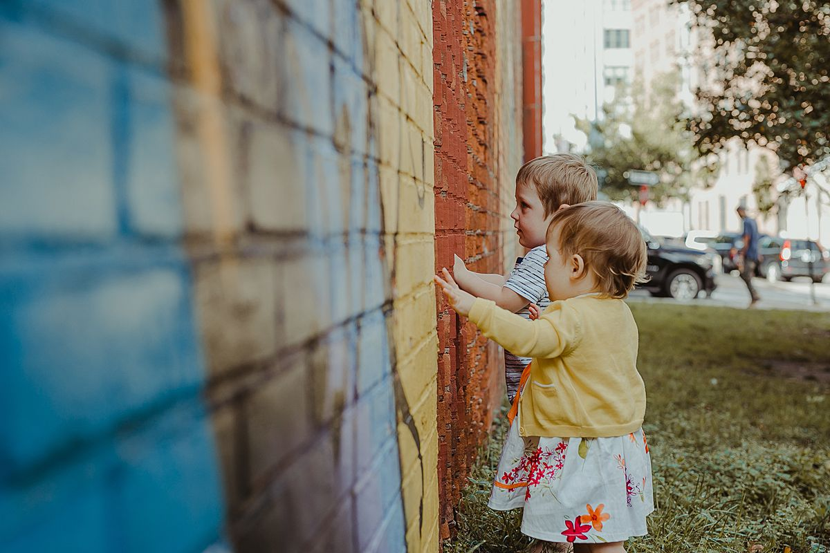 siblings explore colorful graffiti wall in dumbo brooklyn. image by nyc family photographer krystil mcdowall
