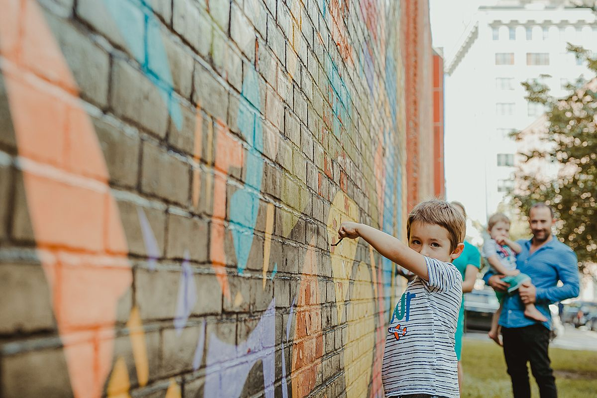 boy plays with sticks against graffiti wall in dumbo brooklyn. image by nyc family photographer krystil mcdowall