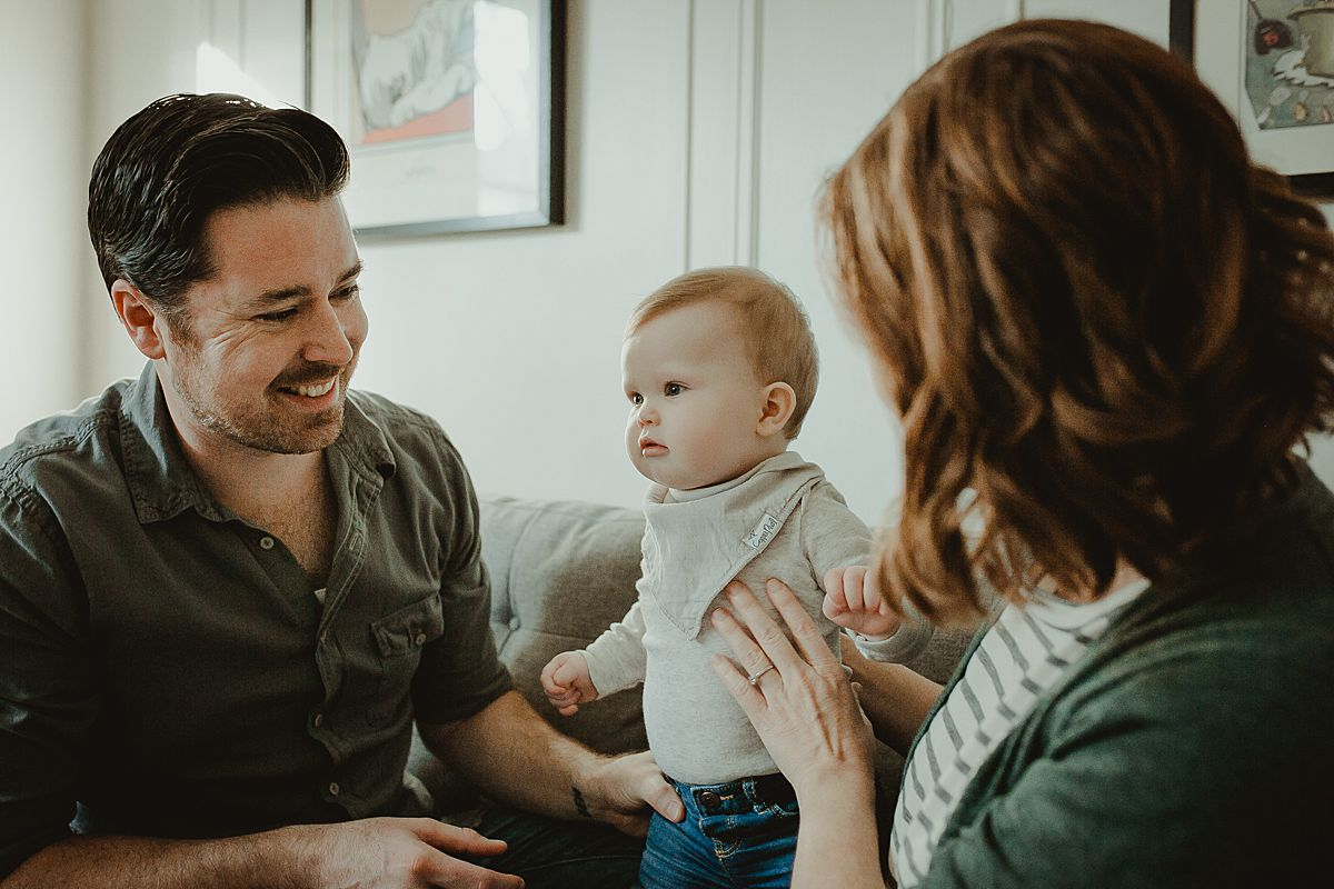 Candid photo of family of three in living room of Queens nyc apartment with baby smiling and parents lovingly smiling at baby